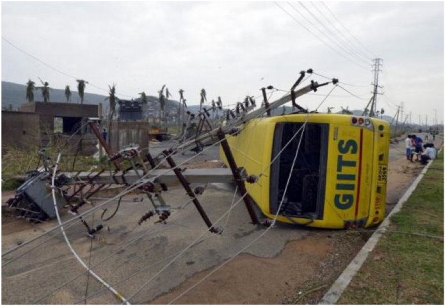 Power lines and a passenger bus are seen after being damaged by strong winds caused by Cyclone Hudhud in Visakhapatnam on October 13, 2014. Photo: Reuters