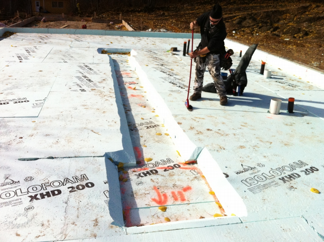 Expanded polystyrene insulation, lots of it, provides R-64 under the concrete slab in this slab-of-grade house. Photo: Alain Hamel