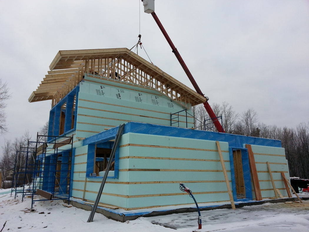 A crane lifting the roof frame into place. Walls are insulated with a combination of mineral wool and EPS. Photo: Alain Hamel